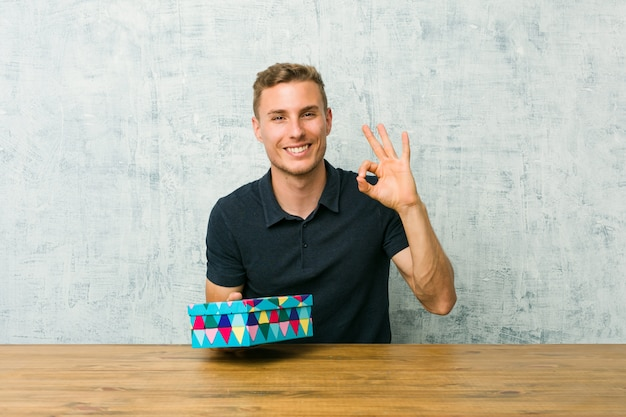 Junger kaukasischer mann, der eine geschenkbox auf einem tisch fröhlich und zuversichtlich hält, die ok geste zeigt.
