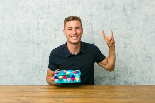 Junger kaukasischer mann, der eine geschenkbox auf einem tisch hält, der eine hörnergeste zeigt
