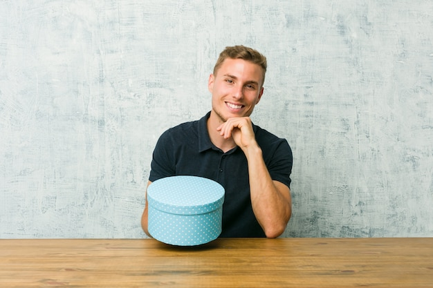 Junger kaukasischer mann, der eine geschenkbox auf einem tisch hält, der glücklich und zuversichtlich lächelt und kinn mit hand berührt.