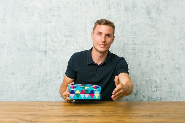 Junger kaukasischer mann, der eine geschenkbox auf einem tisch hält, der hand streckt