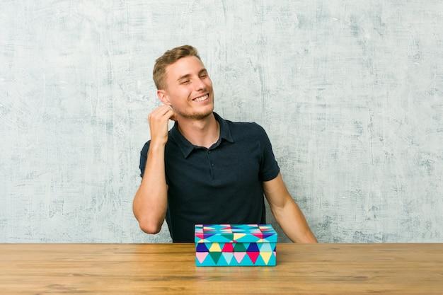 Junger kaukasischer mann, der eine geschenkbox auf einem tisch tanzt und spaß hat.