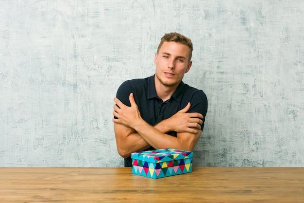 Junger kaukasischer mann, der eine geschenkbox auf einer tabelle geht kalt wegen der niedrigen temperatur oder einer krankheit hält.