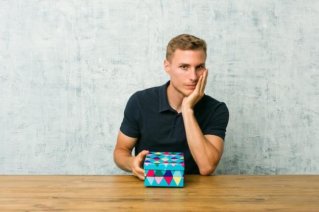 Junger kaukasischer mann, der eine geschenkbox auf einer tabelle hält, die gelangweilt, ermüdet ist und einen entspannungstag benötigt.