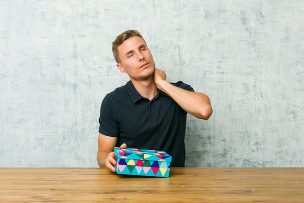 Junger kaukasischer mann, der eine geschenkbox auf einer tabelle leidenden nackenschmerzen wegen des sitzenden lebensstils hält.