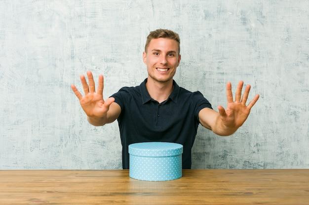 Junger kaukasischer mann, der eine geschenkbox auf einer tabelle zeigt nr. zehn mit den händen hält.