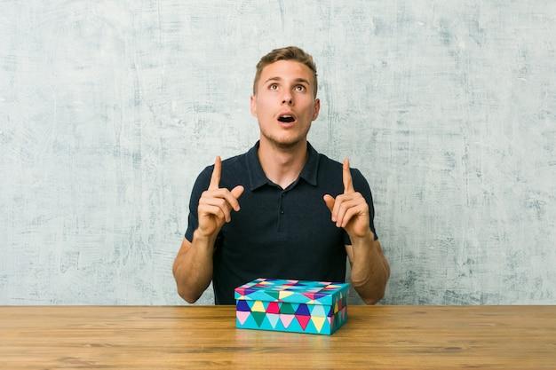Junger kaukasischer mann, der eine geschenkbox auf einer tabelle zeigt oberseite mit geöffnetem mund hält.