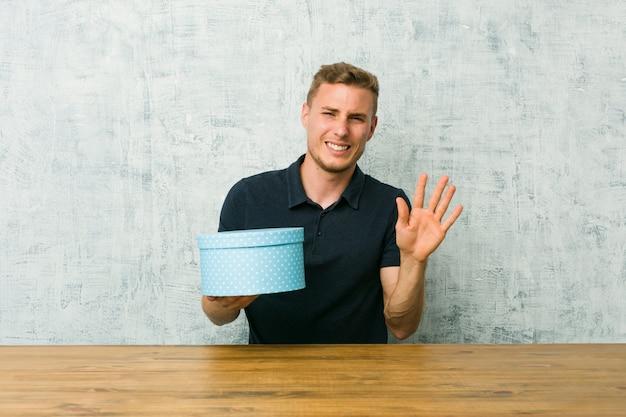 Junger kaukasischer mann, der eine geschenkbox auf einer tabelle zurückweist jemand zeigt eine geste des ekels hält.