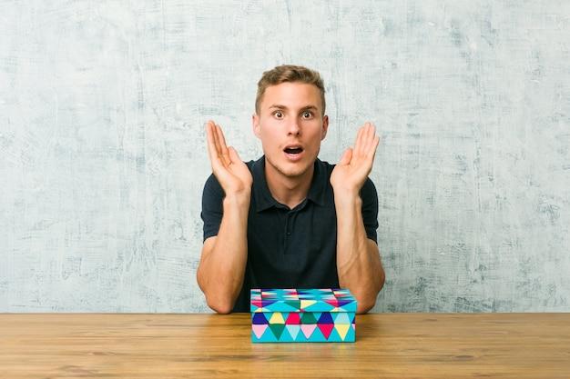 Junger kaukasischer mann, der eine geschenkbox auf tisch hält, überrascht und schockiert.