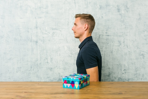 Junger kaukasischer mann, der eine geschenkbox eine tabelle nach links anstarrt, werfen seitlich auf.