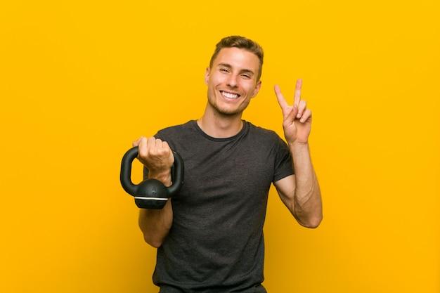 Junger kaukasischer mann, der eine hantel hält, die siegeszeichen zeigt und breit lächelt.