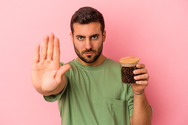 Junger kaukasischer mann, der eine kaffeeflasche isoliert auf rosafarbenem hintergrund hält, die mit ausgestreckter hand steht und ein stoppschild zeigt, was sie verhindert.