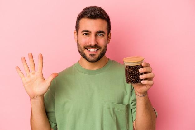 Junger kaukasischer mann, der eine kaffeeflasche isoliert auf rosafarbenem hintergrund hält, lächelt fröhlich und zeigt nummer fünf mit den fingern.