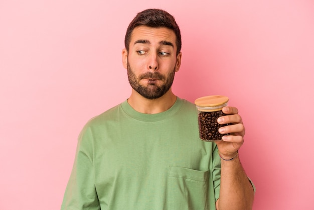 Junger kaukasischer mann, der eine kaffeeflasche lokalisiert auf rosa hintergrund verwirrt hält, fühlt sich zweifelhaft und unsicher.