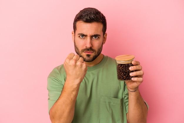 Junger kaukasischer mann, der eine kaffeeflasche lokalisiert auf rosa hintergrund zeigt, der faust zur kamera, aggressiven gesichtsausdruck zeigt.