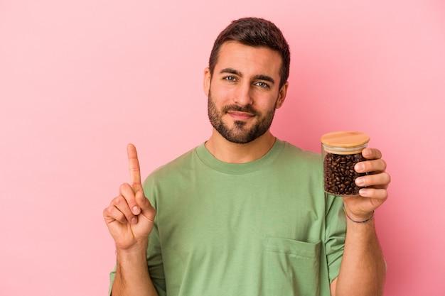Junger kaukasischer mann, der eine kaffeeflasche lokalisiert auf rosa wand zeigt, die nummer eins mit finger zeigt.