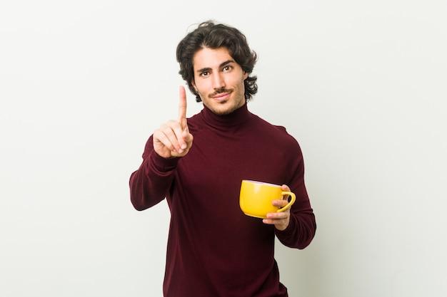 Junger kaukasischer mann, der eine kaffeetasse zeigt nummer eins mit dem finger hält.