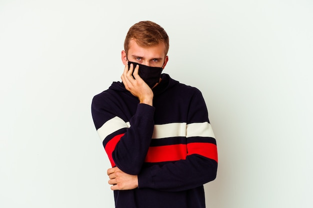 Junger kaukasischer mann, der eine maske für viren trägt, isoliert auf weißem hintergrund, der gelangweilt, müde ist und einen entspannten tag braucht.