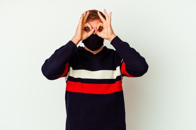 Junger kaukasischer mann, der eine maske für virus lokalisiert auf weiß trägt, das okay zeichen über augen zeigt