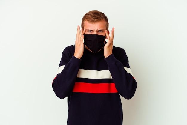 Junger kaukasischer mann, der eine maske für virus trägt, die auf weiß isoliert wird, konzentrierte sich auf eine aufgabe, wobei zeigefinger den kopf zeigen.