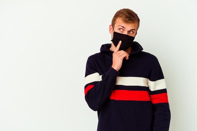 Junger kaukasischer mann, der eine maske für virus trägt, isoliert auf weißem seitwärts mit zweifelhaftem und skeptischem ausdruck.
