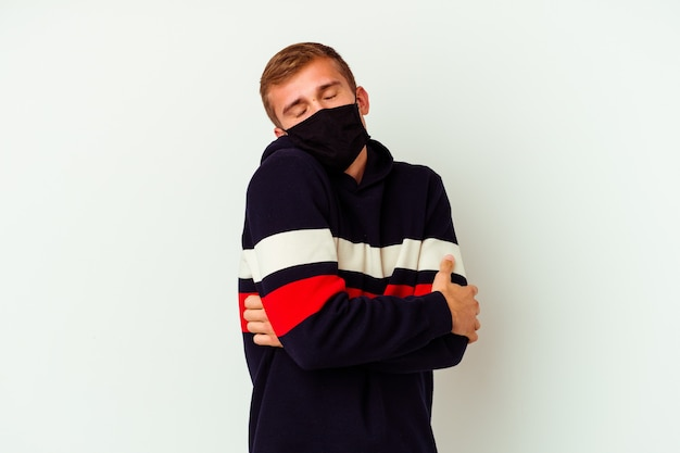 Junger kaukasischer mann, der eine maske für virus trägt, lokalisiert auf weißen wandumarmungen, sorglos lächelnd und glücklich.