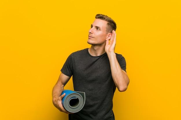 Junger kaukasischer mann, der eine matte versucht, einen klatsch zu hören hält.