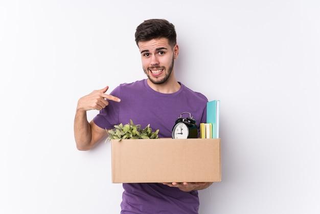 Junger kaukasischer mann, der eine neue nach hause isolierte person bewegt, die von hand auf einen hemdkopierraum zeigt, stolz und zuversichtlich