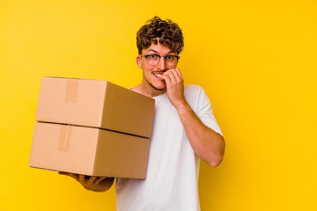Junger kaukasischer mann, der eine pappschachtel lokalisiert auf gelbem hintergrund beißt fingernägel, nervös und sehr besorgt hält.