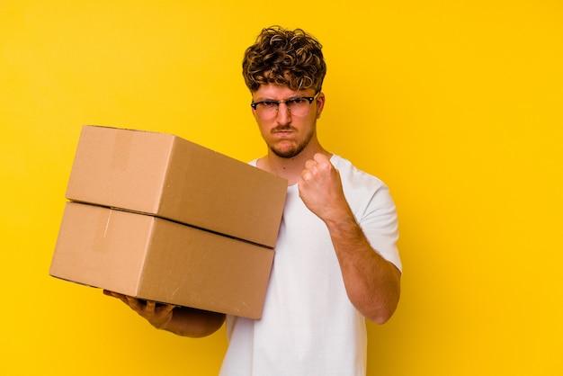 Junger kaukasischer mann, der eine pappschachtel lokalisiert auf gelbem hintergrund hält, der faust zur kamera, aggressiven gesichtsausdruck zeigt.