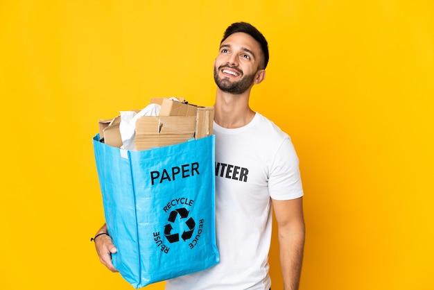 Junger kaukasischer mann, der eine recycling-tasche voll papier hält, um lokalisiert auf weißem hintergrund zu denken, der eine idee beim nachschlagen denkt