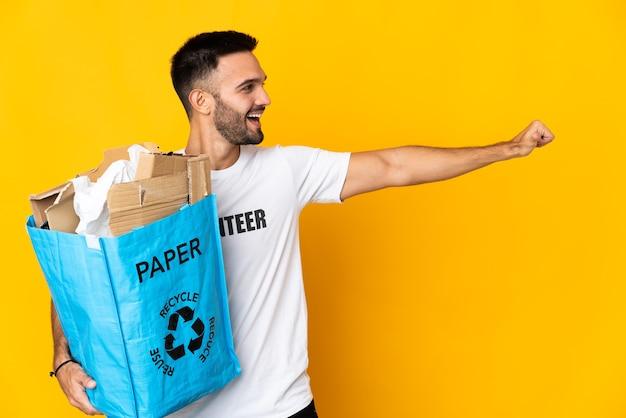Junger kaukasischer mann, der eine recyclingtüte voller papier hält, die isoliert auf weißem hintergrund recycelt wird und eine geste mit dem daumen nach oben gibt