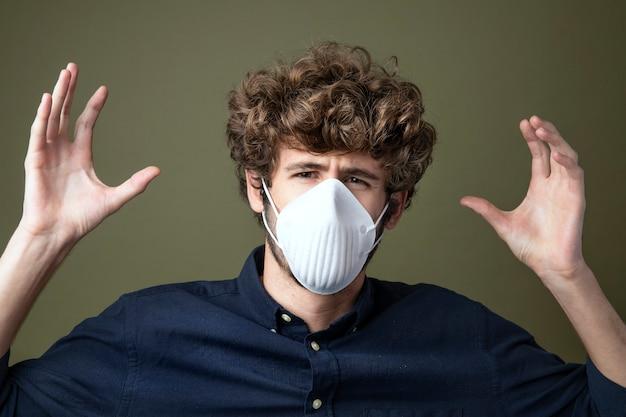 Junger kaukasischer mann, der eine schutzmaske trägt und an luftverschmutzung leidet