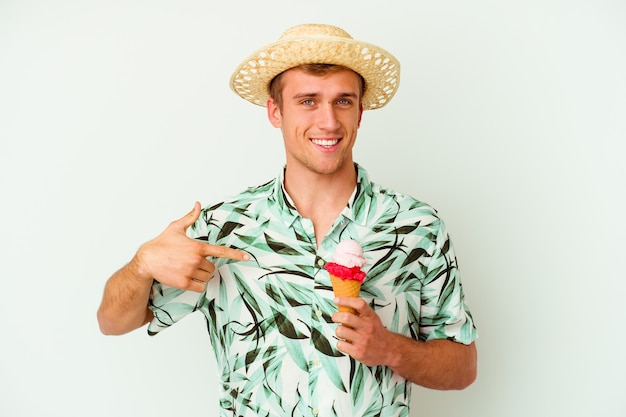 Junger kaukasischer mann, der eine sommerkleidung trägt und ein eis hält, das auf weiße wandperson lokalisiert wird, die von hand auf einen hemdkopierraum zeigt, stolz und zuversichtlich