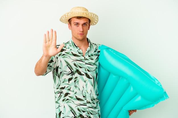 Junger kaukasischer mann, der eine sommerkleidung trägt und eine luftmatratze hält, die isoliert auf weiß steht, mit ausgestreckter hand, die ein stoppschild zeigt und sie verhindert