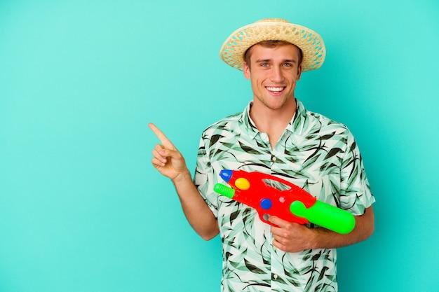 Junger kaukasischer mann, der eine sommerkleidung trägt und wasserpistole lokalisiert auf weißem lächeln und beiseite zeigt, zeigt etwas an der leeren stelle.