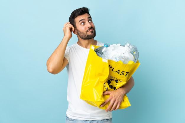 Junger kaukasischer mann, der eine tasche voller plastikflaschen hält, um auf der blauen wand zu recyceln, die zweifel und mit verwirrendem gesichtsausdruck hat