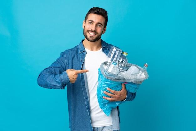 Junger kaukasischer mann, der eine tasche voller plastikflaschen hält, um isoliert auf blau zu recyceln und es zu zeigen