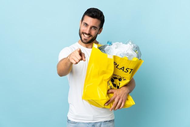 Junger kaukasischer mann, der eine tasche voller plastikflaschen hält, um isoliert auf blauen punktfinger auf sie mit einem selbstbewussten ausdruck zu recyceln
