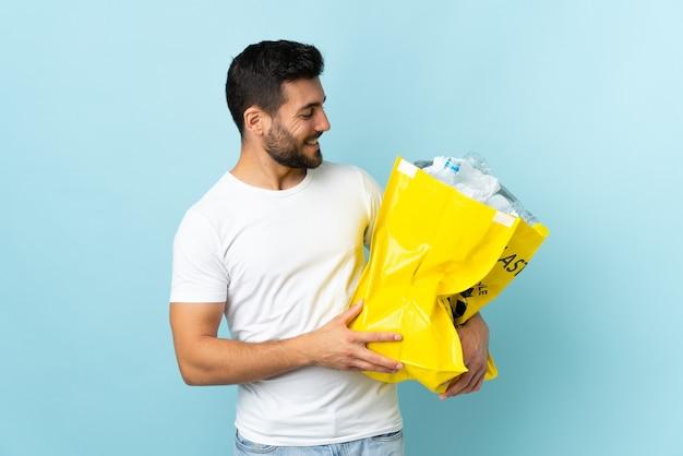 Junger kaukasischer mann, der eine tasche voller plastikflaschen hält, um lokalisiert auf blau mit glücklichem ausdruck zu recyceln