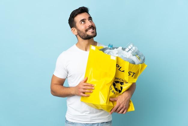 Junger kaukasischer mann, der eine tasche voller plastikflaschen hält, um lokalisiert auf blau zu suchen, während sie oben lächelnd zu recyceln