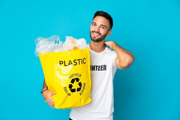 Junger kaukasischer mann, der eine tasche voller plastikflaschen hält, um lokalisiert auf blauem hintergrund lachend zu recyceln