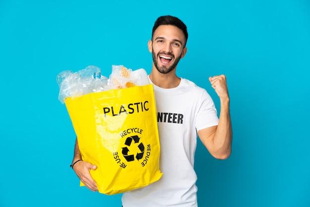 Junger kaukasischer mann, der eine tasche voller plastikflaschen hält, um lokalisiert auf blauem hintergrund zu recyceln, der einen sieg in der siegerposition feiert