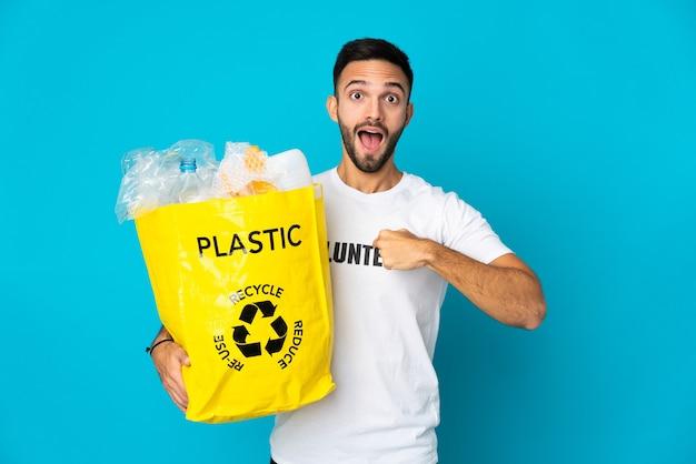 Junger kaukasischer mann, der eine tasche voller plastikflaschen hält, um lokalisiert auf blauer wand mit überraschendem gesichtsausdruck zu recyceln