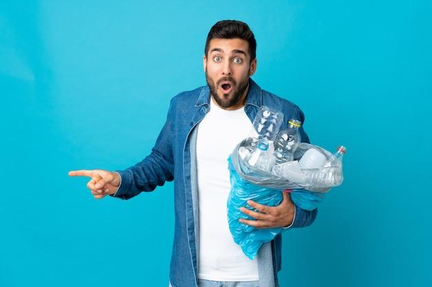 Junger kaukasischer mann, der eine tasche voller plastikflaschen hält, um lokalisiert auf der blauen wand überrascht und zeigende seite zu recyceln