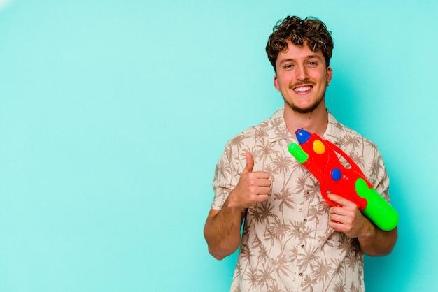Junger kaukasischer mann, der eine wasserpistole auf blauem hintergrund isoliert hält, lächelt und hebt den daumen nach oben