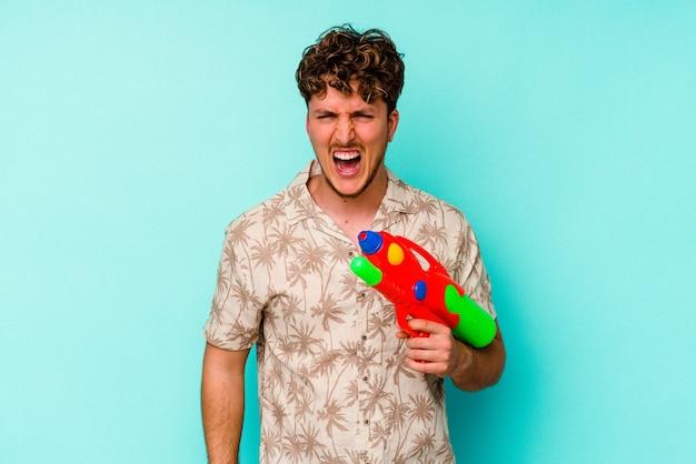 Junger kaukasischer mann, der eine wasserpistole hält, die auf der blauen wand lokalisiert wird, die sehr wütend und aggressiv schreit.