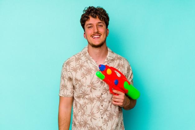 Junger kaukasischer mann, der eine wasserpistole lokalisiert auf blauer wand glücklich, lächelnd und fröhlich hält.