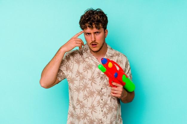 Junger kaukasischer mann, der eine wasserpistole lokalisiert auf blauer wand hält, die eine enttäuschungsgeste mit zeigefinger zeigt.