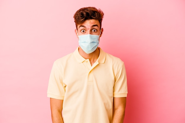 Junger kaukasischer mann, der einen auf rosafarbenem hintergrund isolierten schutz für coronavirus trägt, zuckt mit den schultern und öffnet die augen verwirrt.