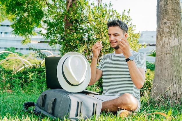 Junger kaukasischer mann, der einen drahtlosen kopfhörer aufsetzt, der auf dem gras sitzt.